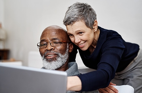 Couple check their fostering finances on a laptop